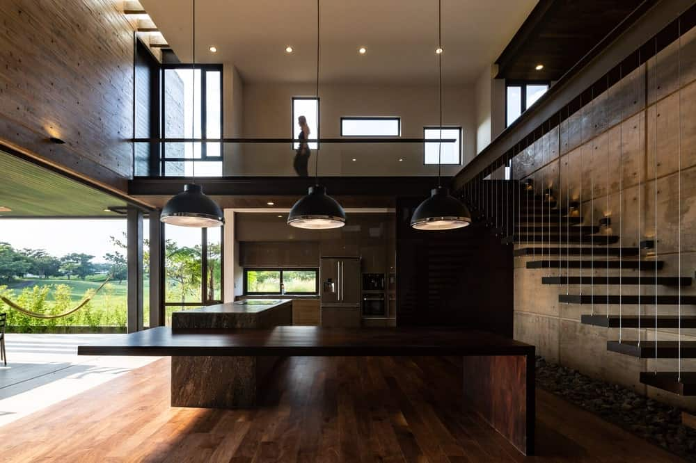A few steps from the covered patio is the interior of the house with a large kitchen by the stairs.