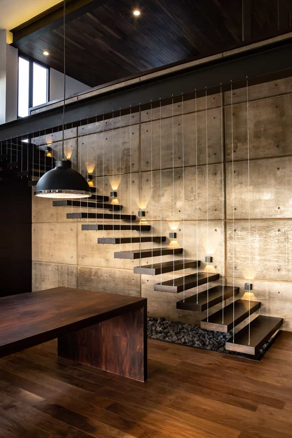 This is a closer look at the stairs with floating steps, modern lighting and gravel underneath.