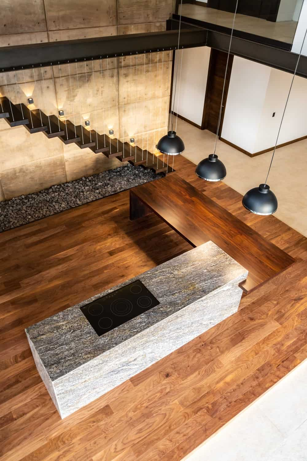 This is a view of the large L-shaped kitchen island from the vantage of the indoor balcony.