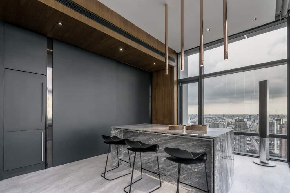 The black structure of the kitchen at the side of the bar and kitchen island can closed to reveal only a large black panel.