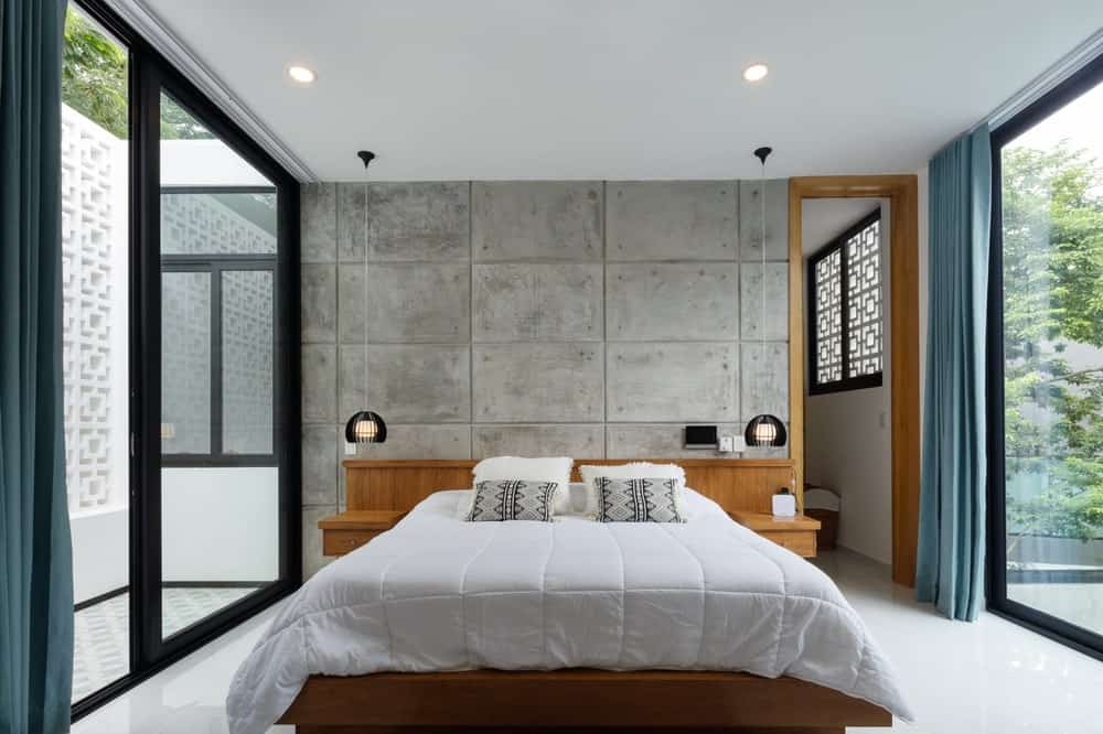 The bed has a wooden frame that is attached to the large wooden headboard extending to the bedside structures.