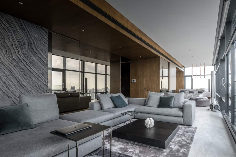 The gray sofa also pairs well with the large gray marble wall panel behind the sofa.