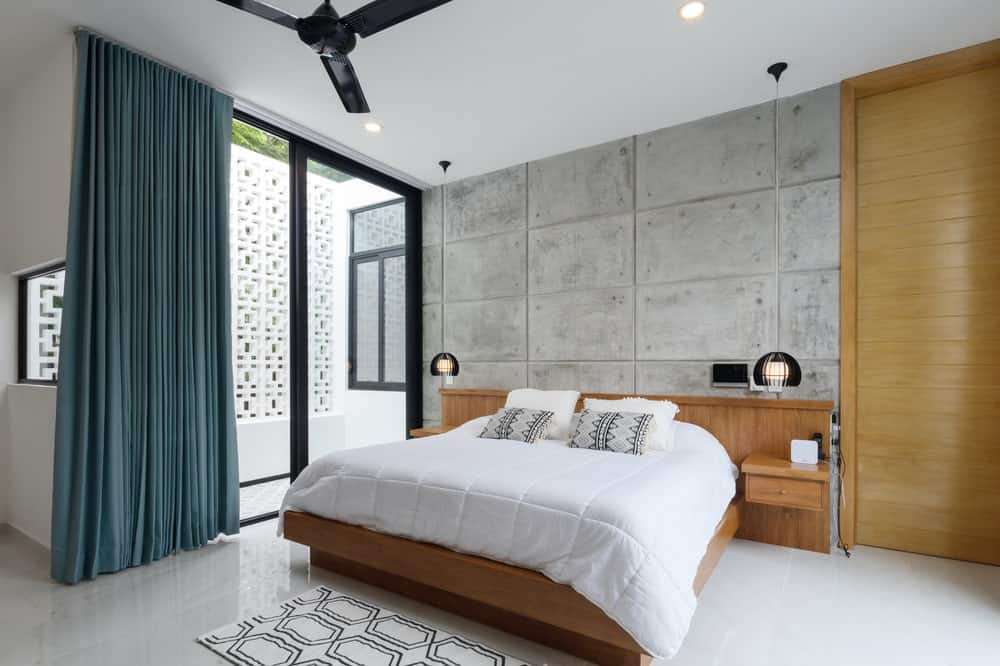 The wooden structure of the bed is adorned with a large textured concrete wall with a wooden panel on the side.