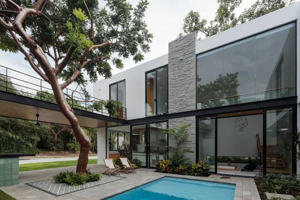 This back view of the house showcases the large glass walls windows and doors that lead to the poolside area and the balcony on the second level.