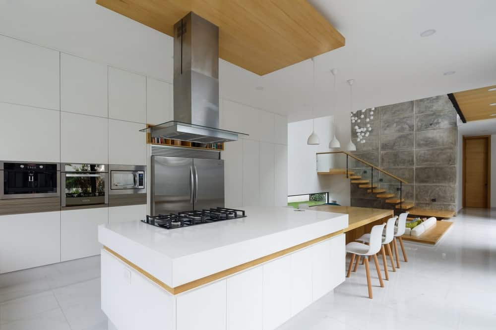 The staonless steel vent of the cooking area matches well with the stainless steel apliances housed by the built-in cabinetry lining the opposite wall.