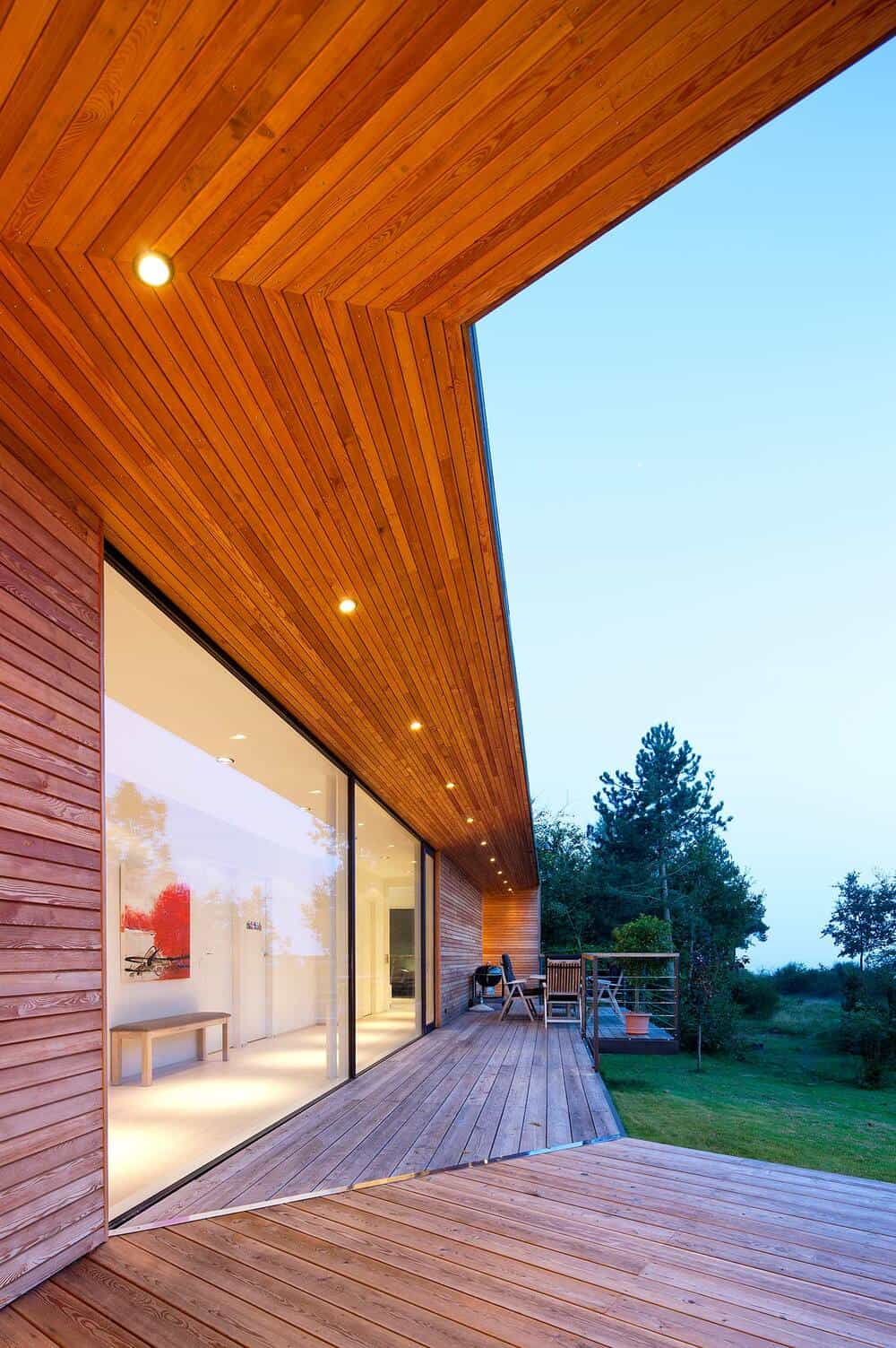The wooden ceiling above the wooden deck walkway has recessed lights.