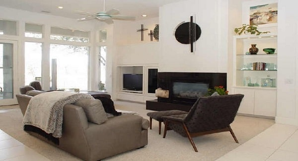 The family room has gray seats, a flatscreen TV, a modern fireplace, and white built-ins.
