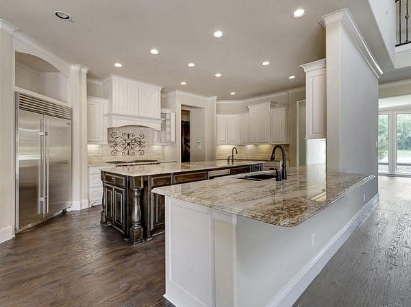 Kitchen with granite countertops, white cabinetry, stainless steel appliances, and a large center island.