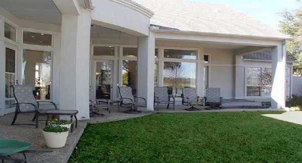 The covered porch has patterned armchairs, matching tables, and fresh potted plants.
