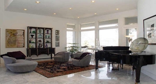 Living room with a grand piano, round seats, wooden display cabinet, and a floral area rug that lays on the marble tiled flooring.