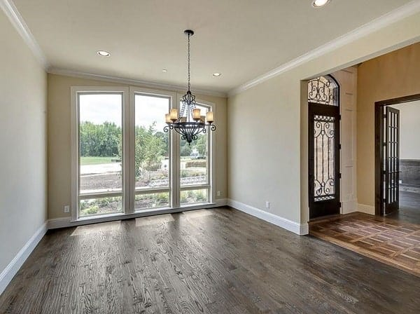 This room has natural hardwood flooring, an ornate chandelier, and floor to ceiling windows overlooking the outdoor scenery.