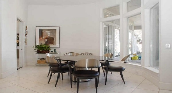 Dining room with a bay window, a contemporary dining set, and a buffet bar adorned with a framed artwork.