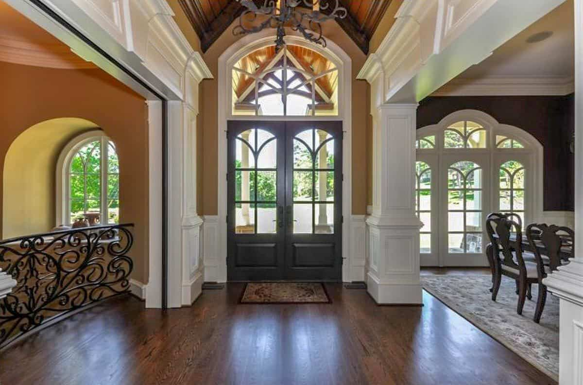 Foyer with a french entry door, an arched transom, and a vaulted ceiling with exposed wood beams.