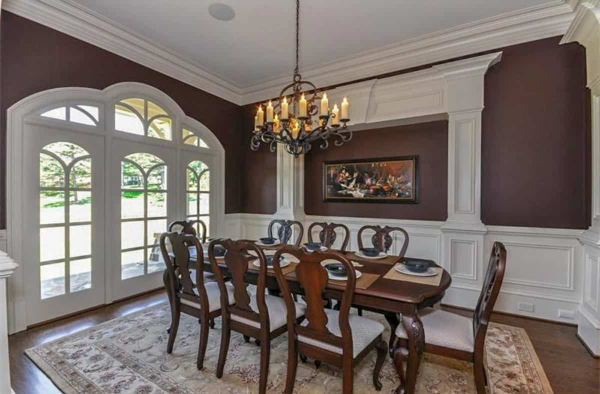 The formal dining room has a wooden dining set, an ornate chandelier, and a framed painting adorning the wainscoted brown wall.