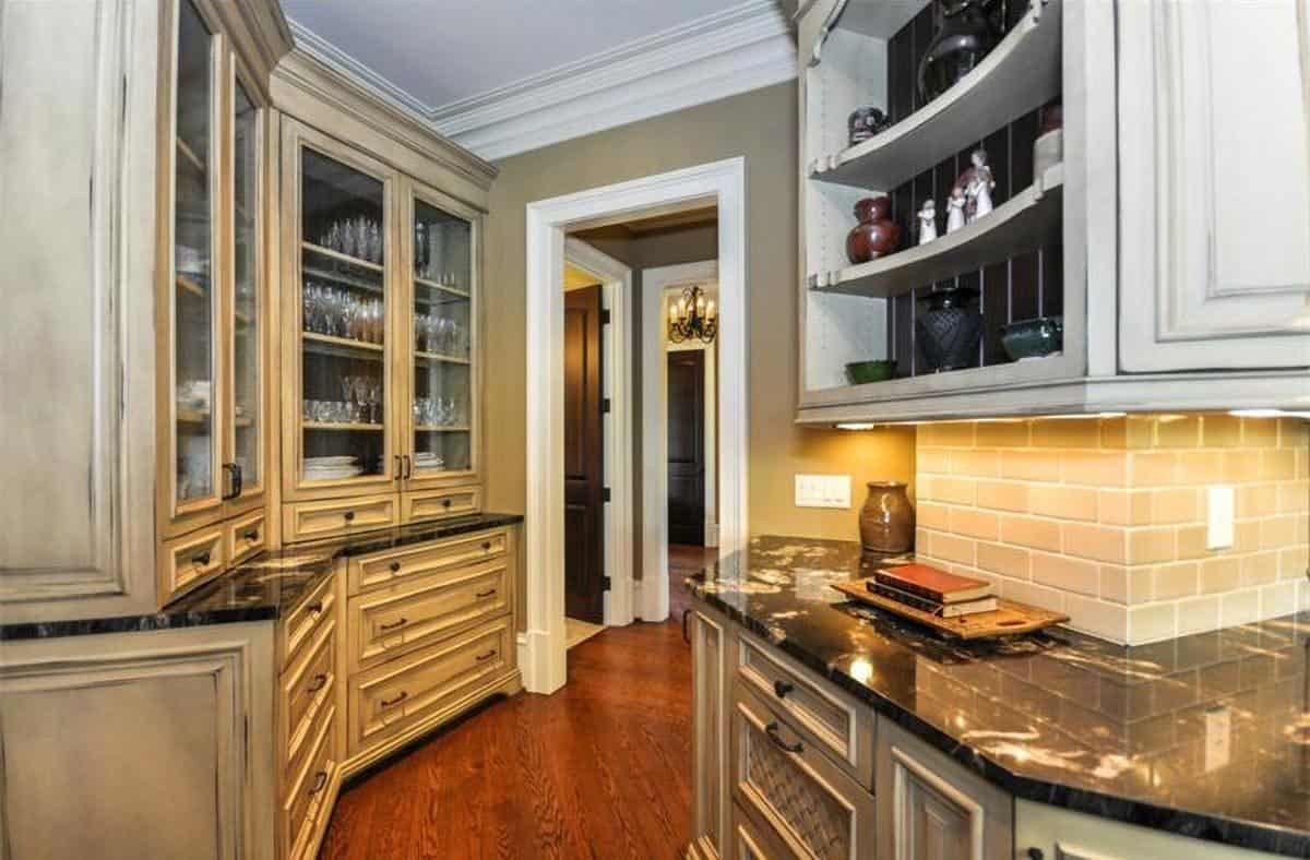 Butler's pantry with granite countertops and glass front cabinets filled with glassware and silverware.