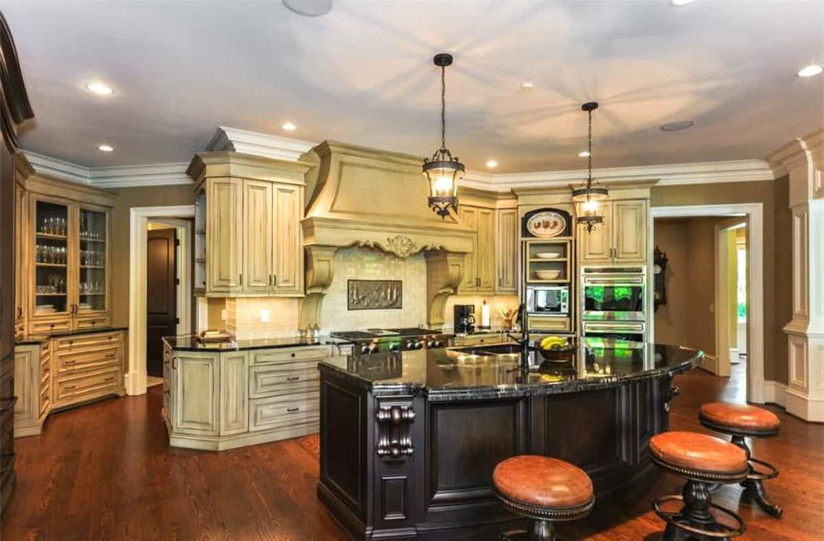 The kitchen is equipped with cream cabinetry, stainless steel appliances, and a black breakfast island.