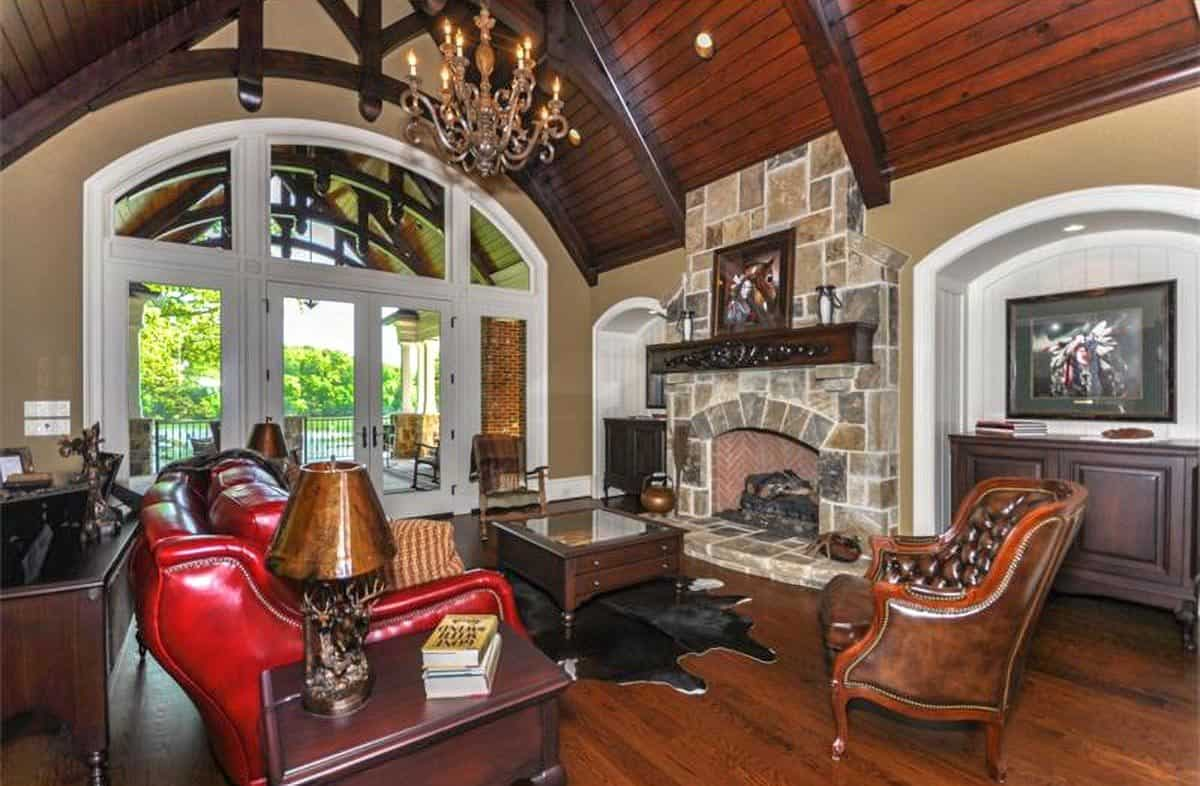 Living room with a stone fireplace, leather seats, wooden tables, and a cowhide rug.