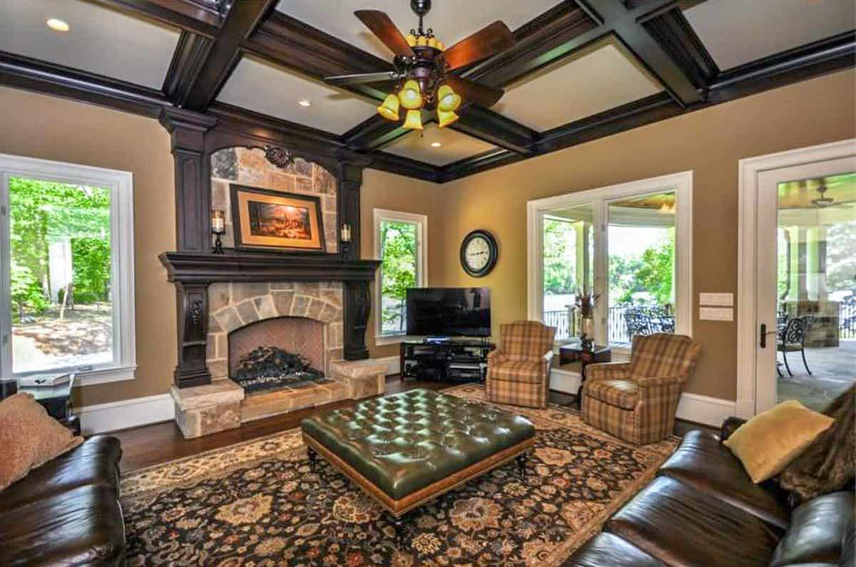 The family room has leather sectionals, checkered armchairs, a tufted ottoman, and a stone fireplace.
