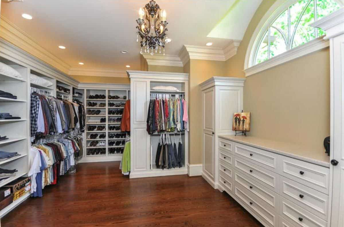 The walk-in closet is filled with white shelvings, built-in cabinets, and a classic chandelier.