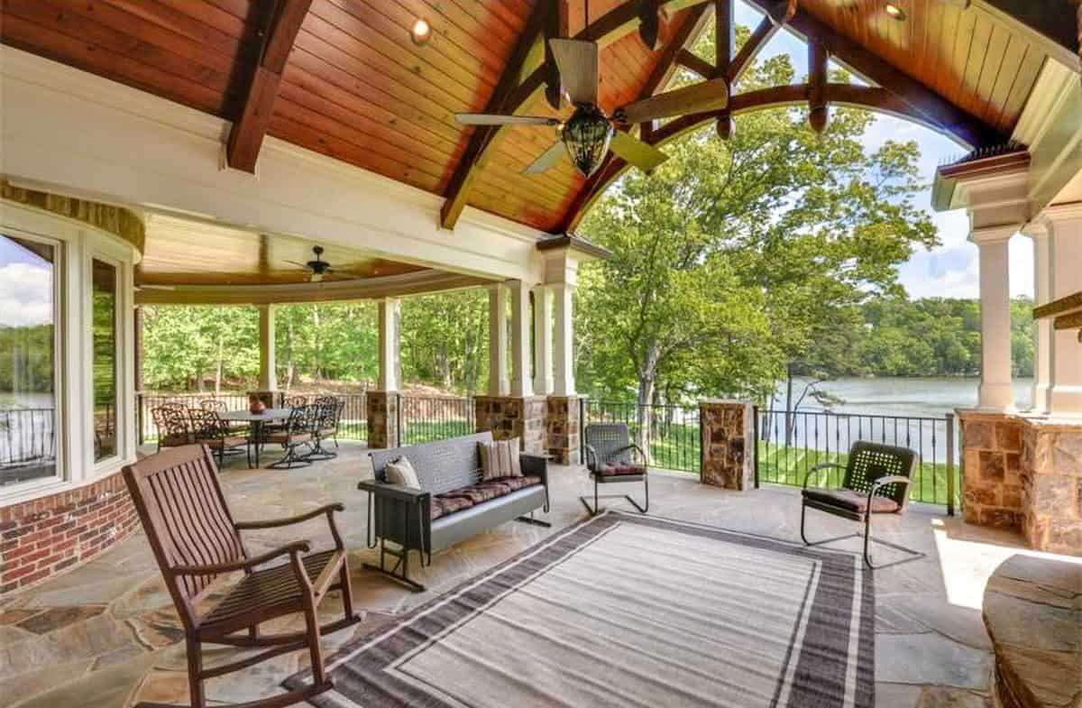 The covered porch has outdoor dining and living overlooking the nearby lake.