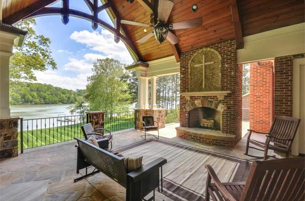 Outdoor living with a brick fireplace, metal sofa, wooden rocking chairs, and a bordered area rug that lays on the flagstone flooring.
