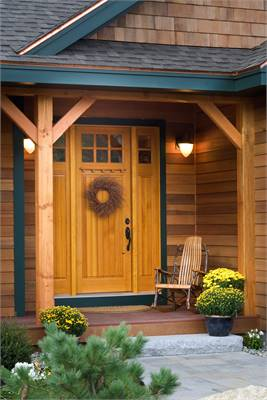 Home entry with a rocking chair and a wooden front door adorned with a wreath.