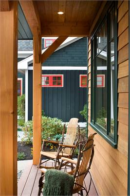 The covered deck is filled with rocking armchairs that blend in with the wood-paneled walls and wide plank flooring.
