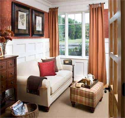 Family room with beige sofa, checkered ottoman, wainscoted walls, and three-panel windows.