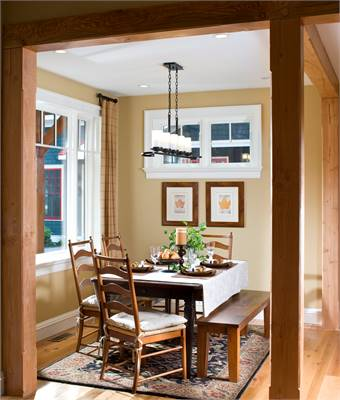The dining room offers a wooden dining table, a matching bench, cushioned chairs, a classic area rug, and a linear chandelier.