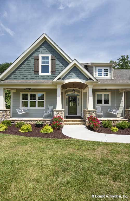 Home entry with covered porch, an arched entryway, and tapered columns.