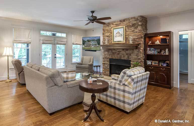 Living room with checkered and beige seats, a glass top coffee table, and a stone fireplace lined with a wooden mantel.