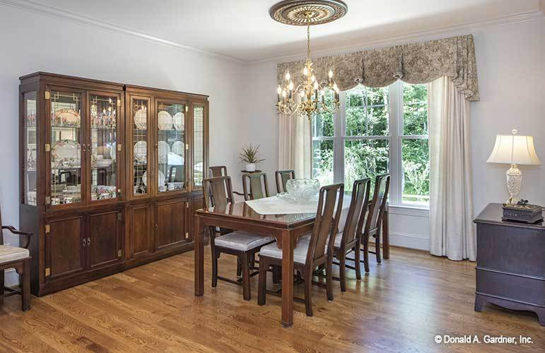 Formal dining room with a china cabinet, a wooden dining table, candle chandelier, and a white framed window dressed in floral valance and white drapes.
