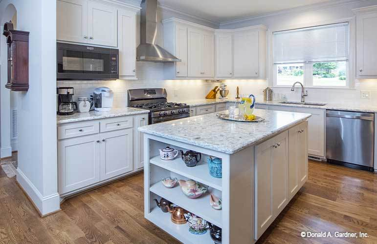 The kitchen is equipped with white cabinets, marble countertops, slate appliances, and a center island.