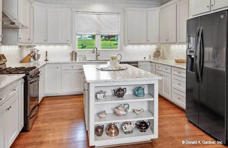 The center island is fitted with built-in shelves that are filled with various style teapots.