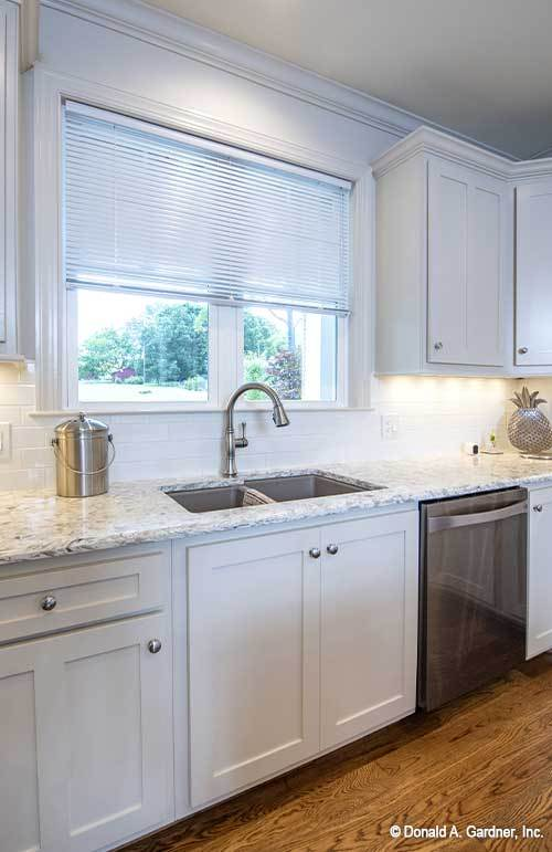 A double bowl sink paired with a gooseneck faucet is placed under the white framed window.