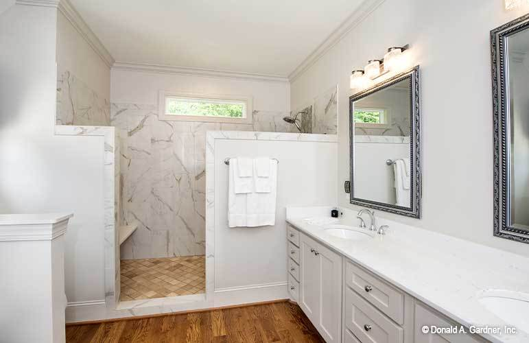 The primary bathroom has a shower area and a dual sink vanity paired with decorative mirrors.