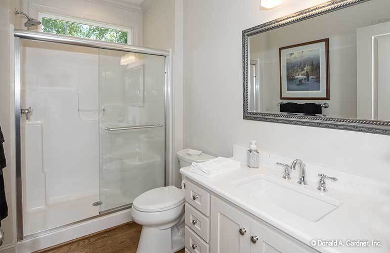 Bathroom with a walk-in shower, a toilet, and white vanity fitted with chrome fixtures and hardware.