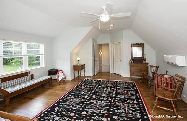 Bonus room with a vaulted ceiling, wooden seats, and a floral area rug that lays on the hardwood flooring.