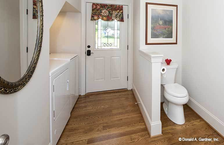 Bathroom with white cabinets and a toilet area adorned with a framed artwork.
