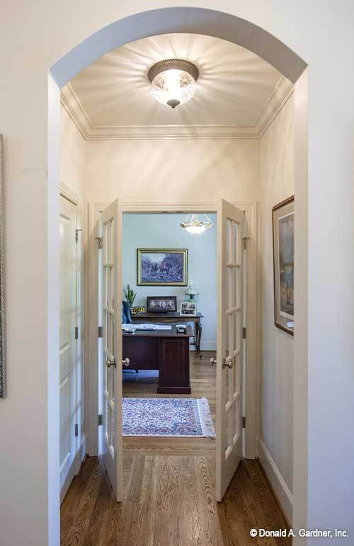 The slim open archway along with a white french door lead to the study.
