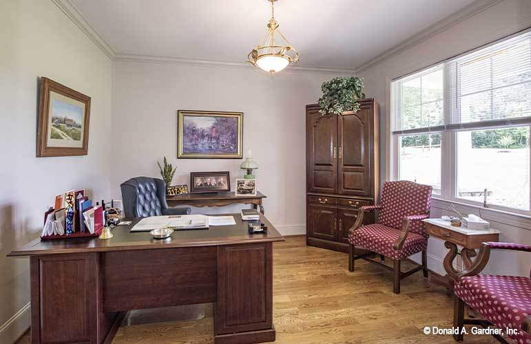 The study is filled with a wooden desk, a wardrobe, red dotted chairs, and a brass dome pendant.
