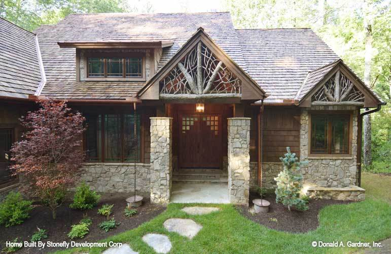 Home facade with a shed dormer, stone accents, wooden double front door, and gable roofs adorned with decorative rustic trims.