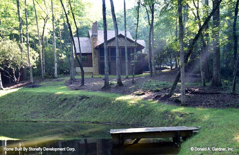 View of the house from the backyard showing the slim trees and a lake complemented with a dock.