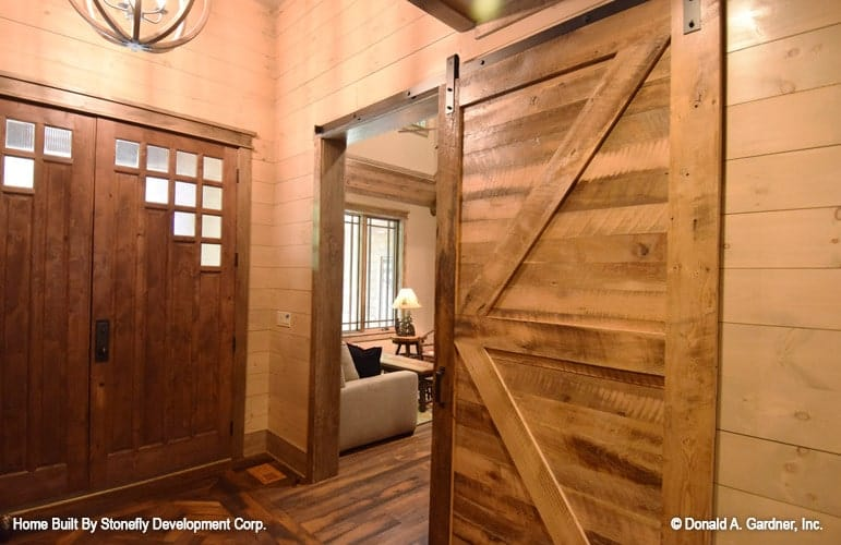 The foyer has a double entry door, a spherical chandelier, and a sliding barn door that opens to the study.