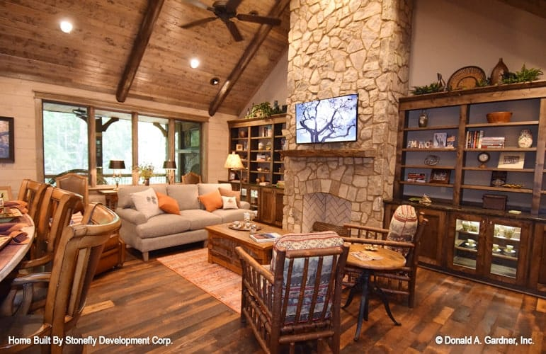 The living room has a stone fireplace, dark wood built-ins, gray sectional, cushioned chairs, and wooden tables.