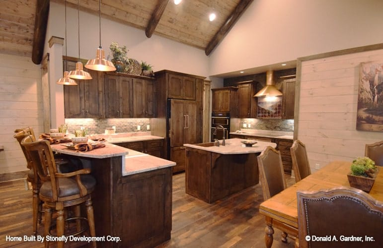 Across the kitchen is the dining room that offers a rectangular dining table and leather high back chairs.