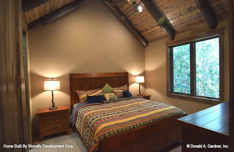 Bedroom with a cathedral ceiling, framed windows, and a wooden bed flanked by matching nightstands.