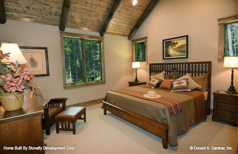 The primary bedroom has wooden furnishings, carpet flooring, vaulted ceiling, and beige walls adorned by framed artworks.