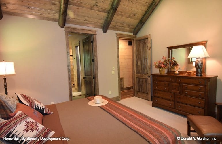 The primary bedroom includes a private bathroom enclosed in a rustic wooden door.