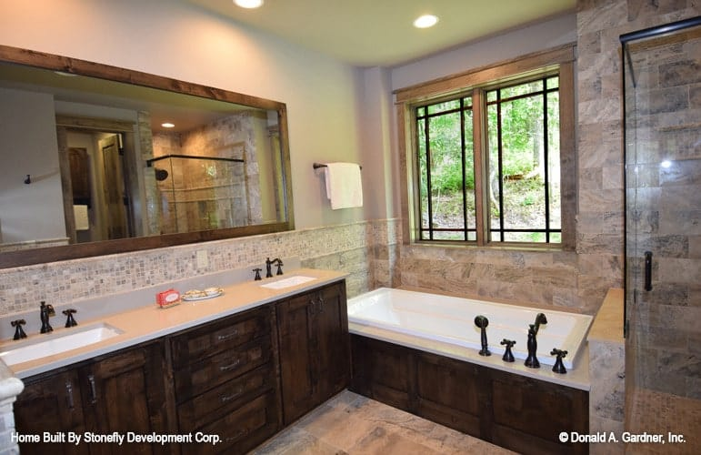 Primary bathroom with a walk-in shower, a drop-in bathtub, and a dual sink vanity.